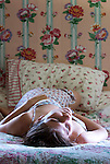 Woman laying in floral bedroom