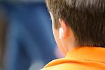 Boy listening to ipod during graduation.