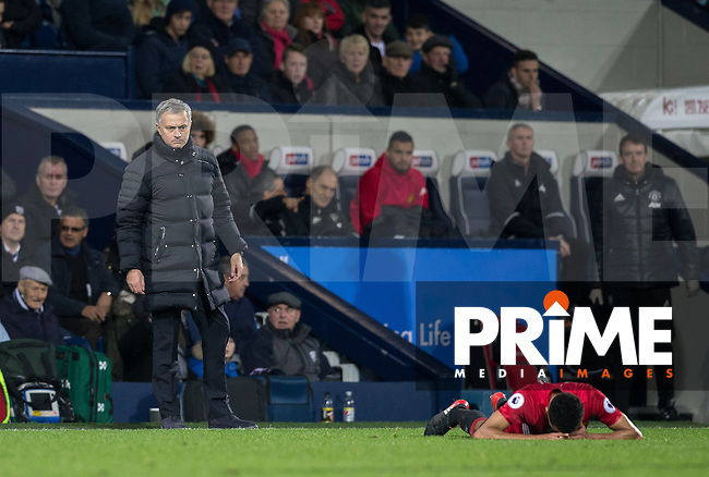 Manchester United Manager Jose Mourinho looks over injured Jesse Lingard of Manchester United during the EPL - Premier League match between West Bromwich Albion and Manchester United at The Hawthorns, West Bromwich, England on 17 December 2016. Photo by Andy Rowland / PRiME Media Images.