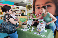 Occidental College UEPI CA Farm to School Program Manager Yelena Zeltser and UEPI Director of Communications Amanda Shaffer (seated) talk to local residents and hand out bags of avocados and taste samples in Mother's Nutritional Center in the Highland Park neighborhood of Los Angeles. The program is intended to promote locally grown fruits and vegetables. (Photo by Marc Campos, Occidental College Photographer)
