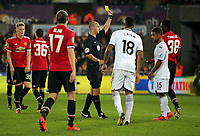 Axel Tuanzebe of Manchester United (R) is shown a yellow card by match referee Robert Madley (C) during the Carabao Cup Fourth Round match between Swansea City and Manchester United at The Liberty Stadium, Swansea, Wales, UK. Tuesday 24 October 2017