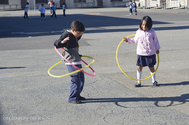 Oakland CA 2nd grade Latino boy playing with hoola hoops at school recess while friend looks on