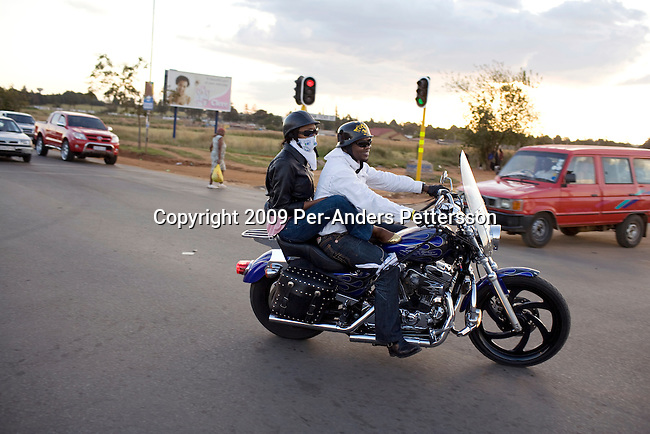 SOWETO, SOUTH AFRICA MARCH 8: Afrika Tau, age 31, rides with a friend on his Harley Davidson motorcycle on March 8, 2009 in Soweto, South Africa. He grew up in Soweto and he is now a successful executive working for Cisco and lives in a house in Kyalami, a wealthy suburb north of Johannesburg. He drives a new BMW and relaxes with his motorbike on the weekends. Afrika is one of the recent educated and affluent black people that has grown up in the poor townships but now are living a middle-class or affluent life in the former white suburbs. (Photo by: Per-Anders Pettersson)