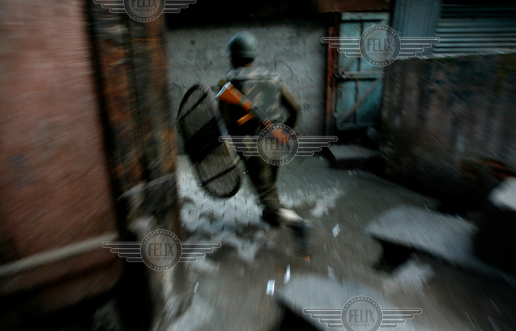 Police and paramilitary chase stone throwing youth through alleyways, following protests over the arrest of  separatist leader Yaseen Malik. Srinagar, Kashmir, India. © Fredrik Naumann/Felix Features