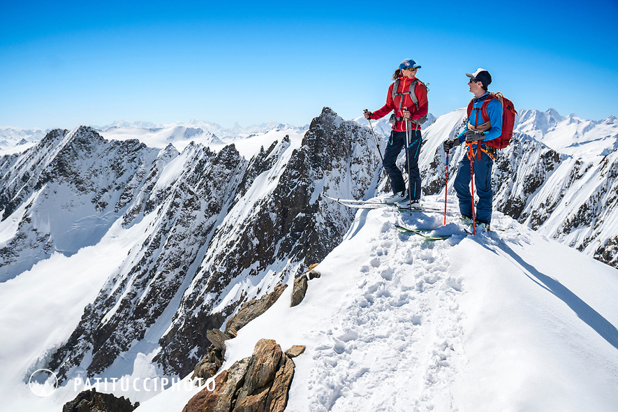 Ski touring from the Susten Pass to the Tierbergli Hut with a climb of the Gwächtenhorn while on the Berner Haute Route, Switzerland. Two skiers stand on the summit.