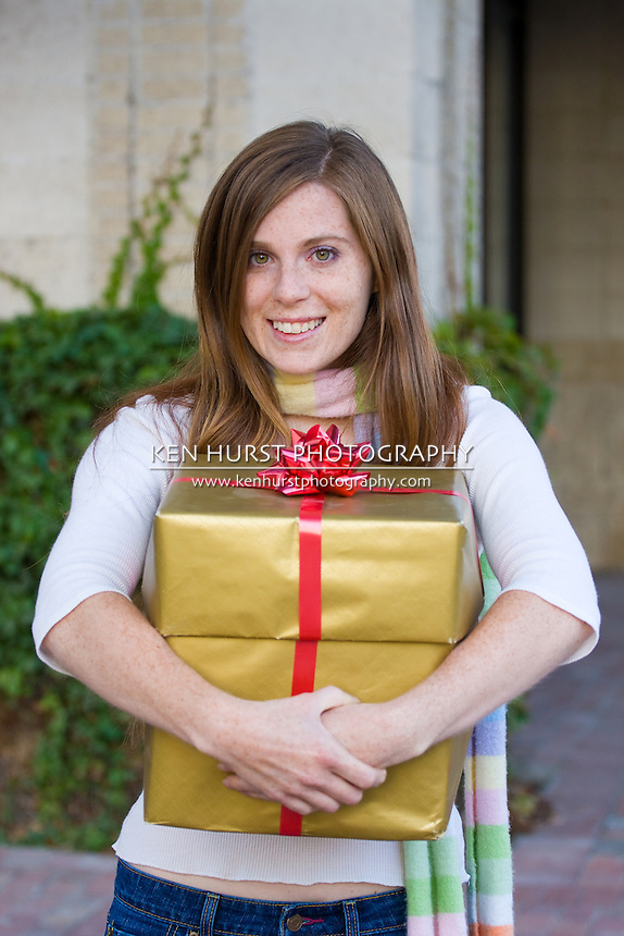 Attractive young happy woman with red hari walking in an urban city environment and holding a Christmas gift wrapped in gold paper.