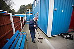 Jack Wolfenden, aged 83, sweeping up rubbish outside dressing rooms at the Harry Williams Riverside Stadium, home to Ramsbottom United after they played Barwell in a Northern Premier League premier division match. This was the club's 13th league game of the season and they were still to record their first victory following a 3-1 defeat, watched by a crowd of 176. Rams bottom United were formed by Harry Williams, the current chairman, in 1966 and progressed from local amateur football  in Bury to the semi-professional leagues.