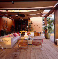 On a terrace shielded by canvas awnings the warm wood floors harmonise with the tones of the traditional plaster walls
