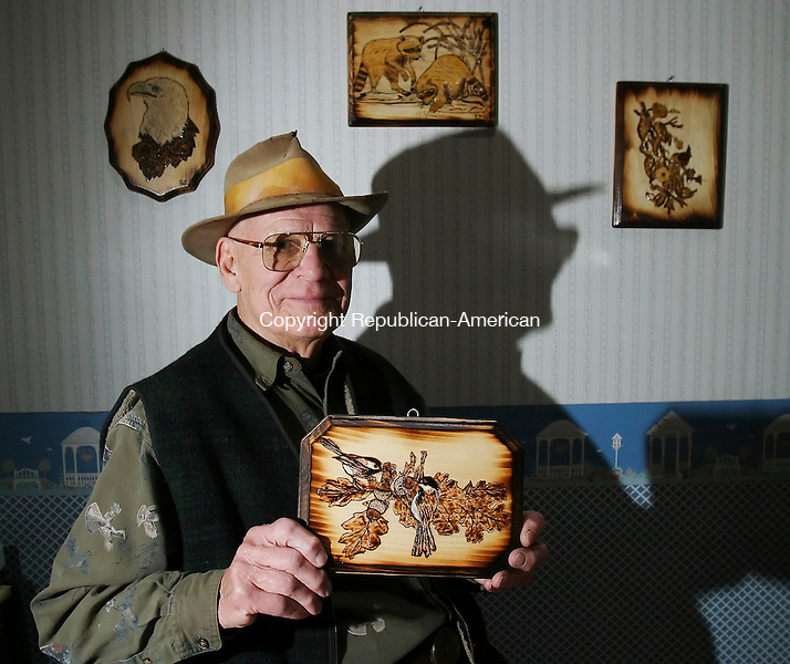 NAUGATUCK, CT 4/2/07- 040207BZ01- Frank Szczesiul, of Naugatuck, pose sin his home holding one of the wood burnings he created.  Szczesiul carves and burns wood as a hobby.<br /> Jamison C. Bazinet Republican-American