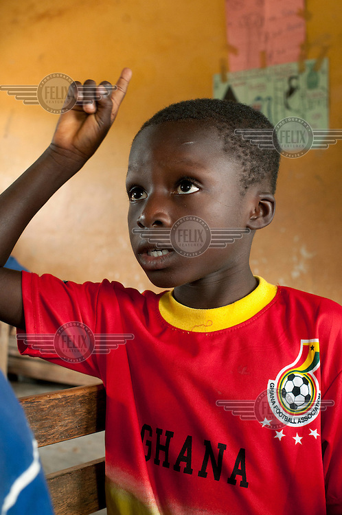 A young pupil raises his hand during a lesson at the Afofusa Presby School.