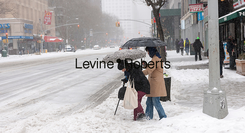 An elderly women is assisted in crossing Eighth Avenue through the snow in the Chelsea neighborhood of New York on Tuesday, March 14, 2017. Originally predicted as a blizzard with up to 20 inches of snow the storm has changed its course and only 4 to 6 inches of snow, sleet and rain are expected, accompanied by howling winds of course. (© Richard B. Levine)