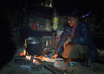 Domo Tamang heats water for tea in the predawn darkness in the village of Gatlang, in the Rasuwa District of Nepal.