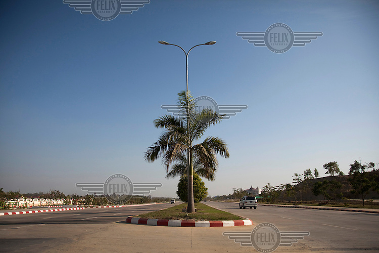 A car drives down an empty street in Naypyitaw, the new capital of Burma (Myanmar) since November 2005.