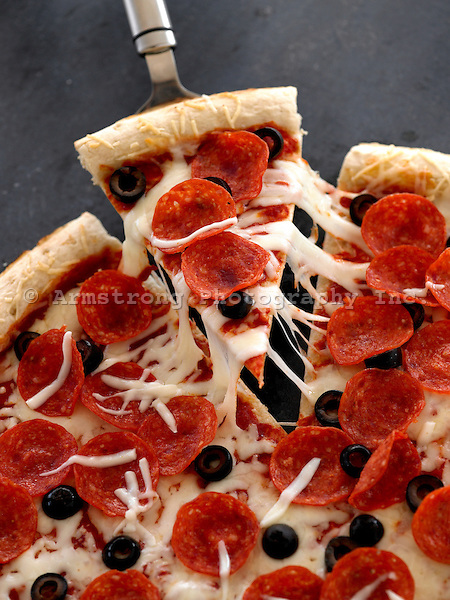 Pepperoni black olive pizza with red tomato sauce and mozzarella cheese, with a slice being removed.