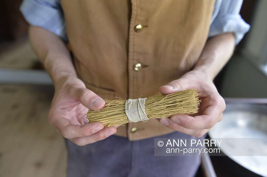 Old Bethpage, New York, USA. August 30, 2015. Matt, a staff member wearing traditional style American clothing, holds a small corn broom during a tour of the Powell House during the Old Time Music Weekend at Old Bethpage Village Restoration. The house was built in 1750 and is restored to its expanded 1855 size, and is the only building standing on its original location in the village.
