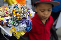 Hundreds march through the streets of the South Bronx in  New York for the Moms Demand Action for Gun Sense march and rally on Saturday, May 11, 2013. The event pays tribute to mothers of gun violence victims during the Mother's Day weekend and calls on elected officials to pass gun reform legislation.  Many of the participants carried bouquets of eight handmade paper flowers to represent the eight children killed by gun violence every day in the United States. (© Frances M. Roberts)