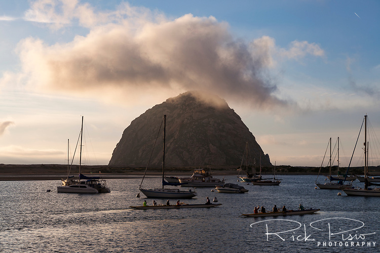War canoes ply the water of Morro Bay at sunset