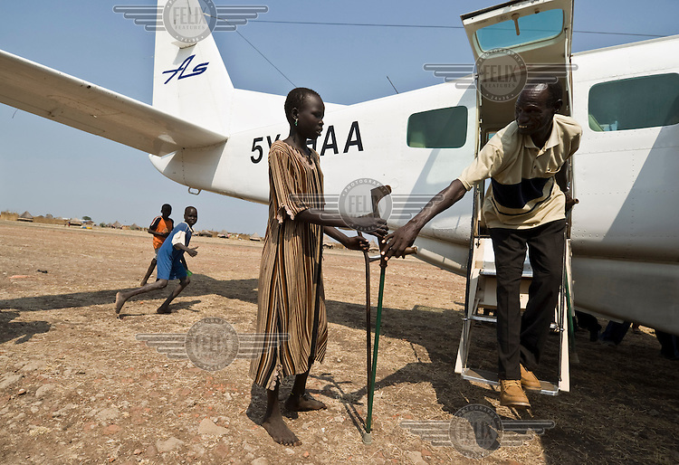 A man with an amputated leg steps out of an aeroplane as he arrives back from the South Sudanese capital Juba where he received prostheses. He was treated after stepping on a landmine. There are a few roads in South Sudan, which in the rainy season are not passable. Most goods, services and personnel are transported by air. ....