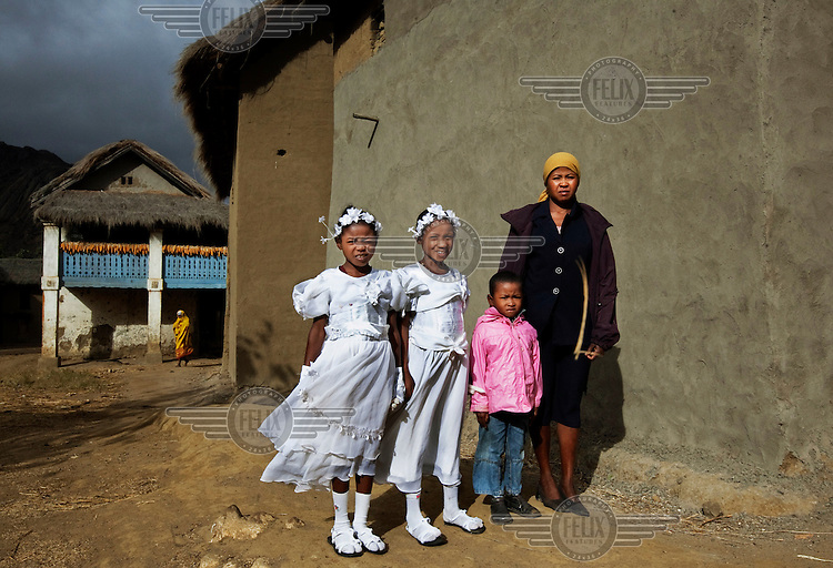 A woman and her three children, dressed in their church clothes, on their way to Sunday service to receive Communion.