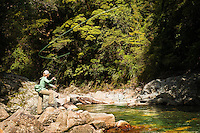 An angler casts a fly to a sighted brown trout on a river in Kahurangi National Park, South Island, New Zealand.
