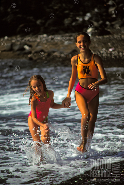 Two young girls running on black sand beach, Big Island of Hawaii