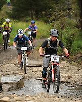 NWA Democrat-Gazette/ANDY SHUPE<br /> Randy Johnson (right) of Bentonvlle leads Jeremiah Middleton of Western Grove across Lee Creek Saturday, Sept. 19, 2015, during the Northwest Arkansas Mountain Bike Championships at Devil's Den State park. Visit nwadg.com/photos to see more photographs from the race.