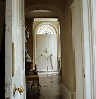View down the stone flagged hall towards the front door with a fanlight window above it