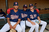 Elizabethton Twins designated hitter Yunior Severino (22) poses for a photo with Jared Akins (12) and Colton Burns (23) in the dugout before a game against the Bristol Pirates on July 28, 2018 at Joe O'Brien Field in Elizabethton, Tennessee.  Elizabethton defeated Bristol 5-0.  (Mike Janes/Four Seam Images)