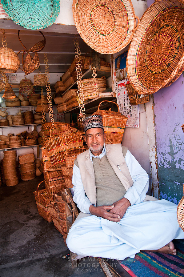 Smiling basket vendor in front of his shop stuffed with wares, Hazratbal area, Srinagar, Kashmir, India.