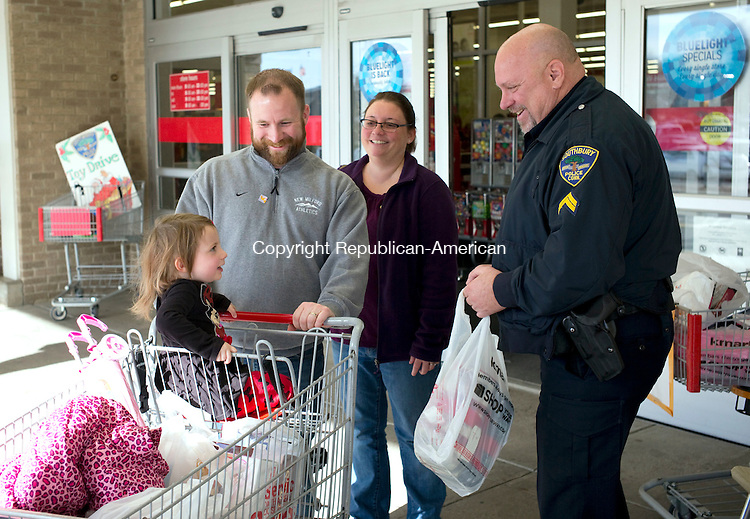 Southbury, CT- 27 November 2015-112715CM06-  Southbury police officer, Cpl. Brian Hughes, right, collects a donation from Ryan Fitzsimmons and his wife, Nicole and their daughter, Erin 2 of Woodbury, during an annual holiday toy drive in front of Kmart at the Southbury Plaza in Southbury Friday.  Police officers and volunteers collected donations of clothing, blankets and toys to help children and families in the Southbury community.   Christopher Massa Republican-American