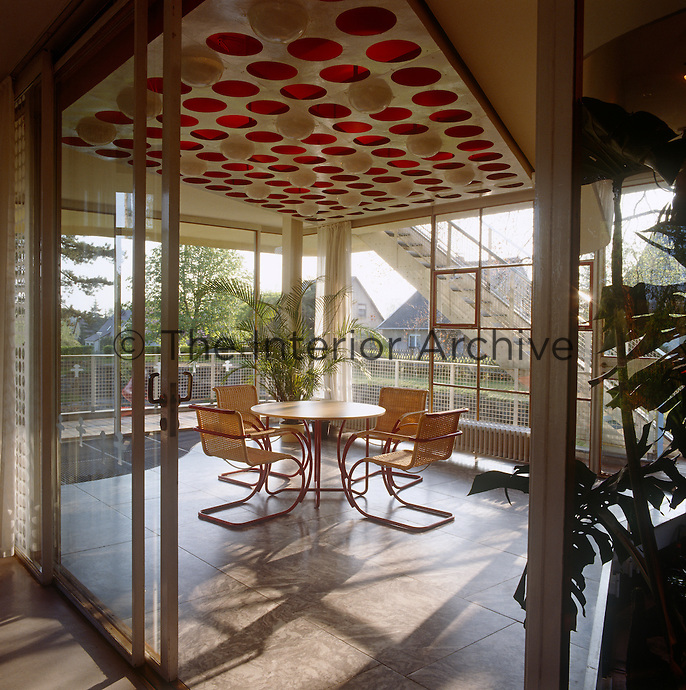 Sliding glass doors between the winter garden and main living area serve to unify the interior and exterior spaces and work with the land and light in illustration of the modernist ethos of architect Hans Scharoun