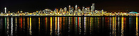 Panorama of Seattle skyline at night with lights reflecting in Elliott Bay, Seattle, Washington State.
