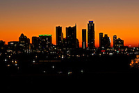 A bright, vivid orange morning sunrise engulfs the city skyline of Austin Texas looking beside the Lake Austin, Colorado River.