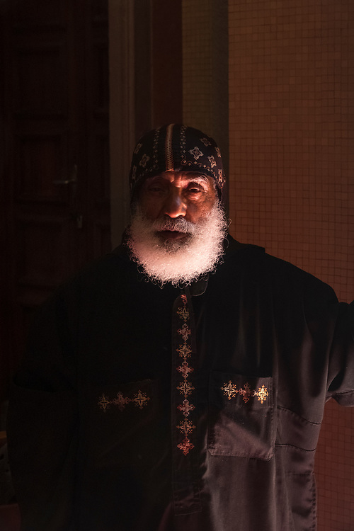 Soft lighting from an open door at the Holy Trinity Cathedral in Addis Ababa illuminates this stately priest inside.