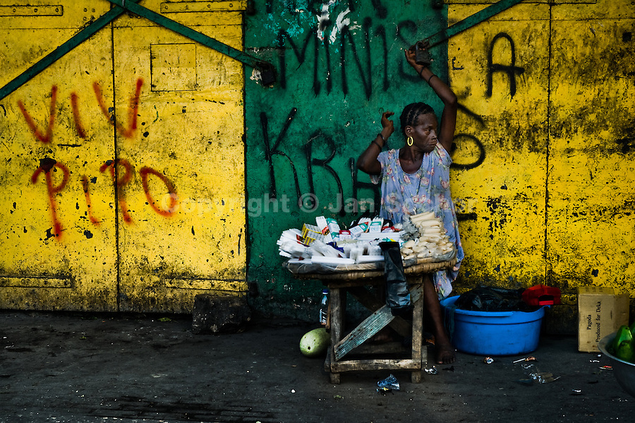 A Haitian woman resell cigarettes and candies in the La Saline market, Port-au-Prince, Haiti, 15 July 2008. Every day thousands of women from all over the city of Port-au-Prince try to resell supplies and food from questionable sources in the La Saline market. The informal sector significantly predominate within the poor Haitian economics and the regular shops virtually do not exist. La Saline is the largest street market area in Port-au-Prince.