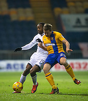 Myles Weston of Wycombe Wanderers battles Jamie McGuire of Mansfield Town during the The Checkatrade Trophy  Quarter Final match between Mansfield Town and Wycombe Wanderers at the One Call Stadium, Mansfield, England on 24 January 2017. Photo by Andy Rowland.