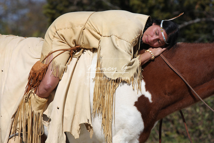 A Native American Indian woman resting on the back of her Indian pony