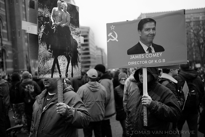 Protestors carry signs mocking FBI director James Comey, Vladimir Putin and Donald Trump on Inauguration Day in Washington, DC on Jan. 20, 2017.
