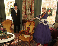 NWA Media/Michael Woods --12/07/2014-- w @NWAMICHAELW...Ben Johnson (left) watches as Hannah Saunders, plays the violin Sunday afternoon during the Christmas celebration at the Headquarters House Sunday afternoon in Fayetteville.  Members of the Heritage School were on hand dressed in period attire to provide christmas music for visitors during the holiday celebration at the historical civil war era home.