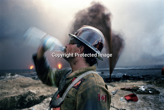 Kerry Fedor, a fire fighter from Calgary, Canada drinks water during a break from putting out oil fires on August 14, 1991. He worked at Greater Burhan oilfield in Kuwait. When the Gulf War ended in February 1991,the Iraqi forces retreated and hundreds of wells were blown up. Expert teams mainly from USA and Canada arrived and the last fires were put out in October 1991. (Photo by: Per-Anders Pettersson)