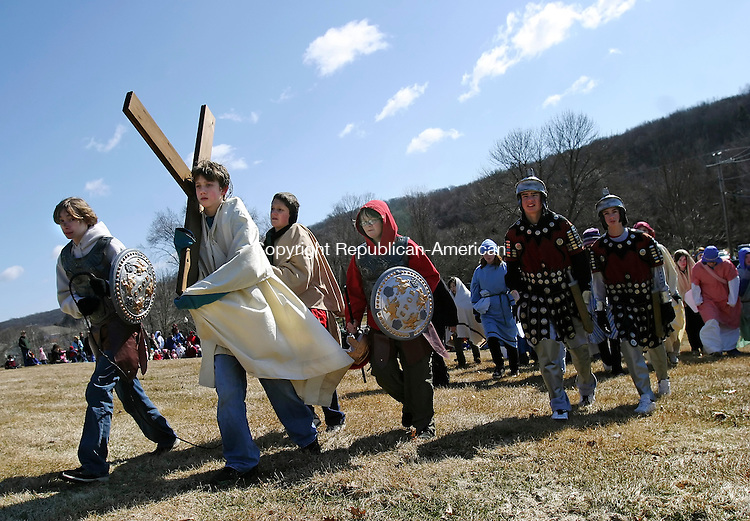 SOUTHBURY, CT 03/21/08- 032108BZ10- Trevor Ferraro, portraying Jesus, carries a cross to the crucifixion while surrounded by Roman guards (from left) Rob Crowdis, Ben Swanson, Henry Archie, and Rick Pitman during the annual Good Friday Faith Walk in Southbury. The boy helping Jesus is unidentified. More than 400 people walked in the procession along Main Street South reenacting the stations of the cross along the way to Sacred Heart Church.<br /> Jamison C. Bazinet Republican-American