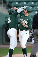 Shortstop Dillon Kark (2) of the Michigan State Spartans, right, is greeted by Zaid Walker (3) after scoring a run in a game against the Merrimack Warriors on Saturday, February 22, 2020, at Fluor Field at the West End in Greenville, South Carolina. Merrimack won, 7-5. (Tom Priddy/Four Seam Images)