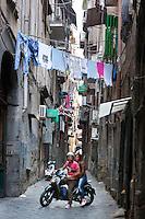 Italy, Campania, Naples: Scooter along narrow alley   Italien, Kampanien, Neapel: Paar mit Motorroller unterwegs durch Neapels enge Gassen