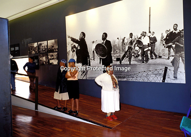digasow00081.South African Places. Gauteng. Unidentified people looking at displays in the newly opened Hector Peterson museum on June 14, 2002 in Soweto, South Africa. Hector Peterson was killed during the student uprising in Soweto in 1976, where black students demonstrated against the Afrikaans language imposed by them by the Apartheid government. The new museum opened on Youth Day June 17, 2002..©Per-Anders Pettersson/iAfrika Photos
