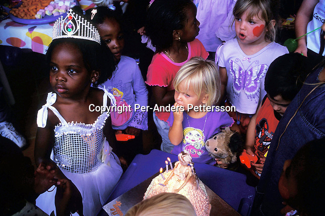 JOHANNESBURG, SOUTH AFRICA - FEBRUARY 29: Lebone Dube, age 4, with her friends at her birthday party on February 29, 2004 in Cedar Lake, a up-market gated community in Johannesburg, South Africa Her father, Oscar Dube, works as a Key Account manager for the Swedish mobile phone equipment maker Ericsson and his wife, Mpho Dube, is fund manager at Old Mutual, an insurance company in SA. They belong to the new black elite in SA. Lebone attends an exclusive pre-school with mostly white children and she invited them for her birthday party. Well educated and connected, they have risen from the poverty in the townships to a very different lifestyle, since the fall of Apartheid and the start of democracy in the country in 1994. .Photo: Per-Anders Pettersson/iAfrika Photos....