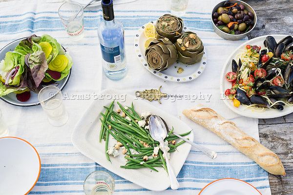 Closeup of an outdoor meal scene at a picnic table. With a bottle of white wine, a plate of string bean salad with cheese and nuts, baguette, a bowl of mixed olives, corkscrew, tableware, and a green salad.