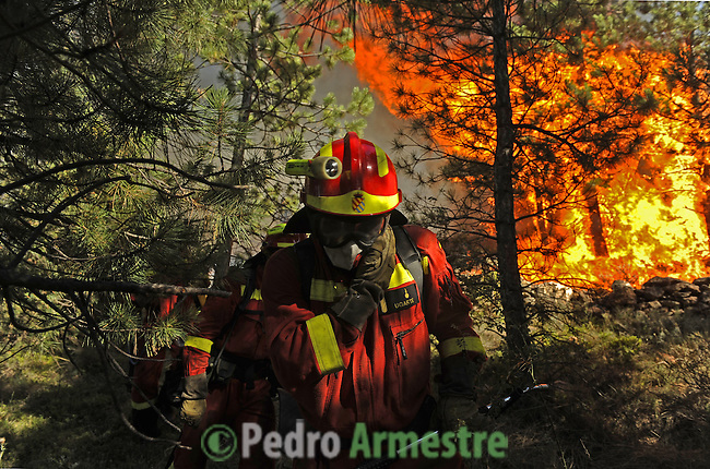 A member of the Spanish Army Emergency Unit (UME) walks around a wildfire burning in Canizar del Olivar near Teruel, on July 24, 2009. Deadly summer wild fires spread across Spain, France, Italy and Greece on Friday with holidaymakers rescued from beaches and thousands of firefighters brought into the battle.on July 24, 2009. (C) Pedro ARMESTRE
