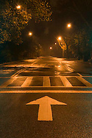 THIS IMAGE IS AVAILABLE EXCLUSIVELY FROM CORBIS.....Please search for image # 42-19639459 on www.corbis.com ....Arrow Sign and Crosswalk on Road in Central Park, Illuminated at Night....New York City, New York State, USA