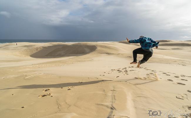 Jumping in the sand dunes. Stockton Beach Sand dunes Worimi Conservation Lands. Anna Bay, Port Stephens, NSW, Australia
