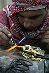 A Palestinian goldsmith works on a piece of jewellery at the Wazwaz family workshop in the West Bank city of Hebron on December 15, 2010. For more than 30 years the Wazwaz family makes jewellery from recycled gold at their refining workshop to sell at over West Bank and abroad. Photo by Mamoun Wazwaz